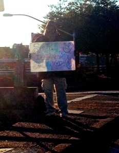 "Homeless Portland man holds sign this morning that  reads, ""SMILE! If I can smile, so can you!"""